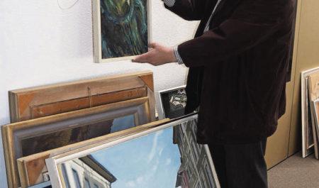 Ruedi Schär beim Aufhängen der Bilder aus dem Besitz der Wiler Kulturstiftung. (Bild: Chris Gilb)